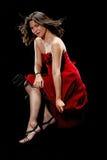 Den nätt kvinnan drar ner fållen av henne klänningen Royaltyfri Foto