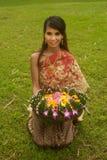Den nätt kvinnan i thailändskt utformar kläder i posera hållblommatakbjälke. arkivfoton