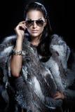 Den nätt kvinnan som ha på sig solglasögon, och härligt pälsfodrar Arkivbild