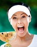 Den nätt tennisspelaren segrade koppen Arkivfoto