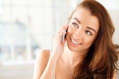 Den nätt unga kvinnan som använder mobil, ringer Royaltyfri Bild