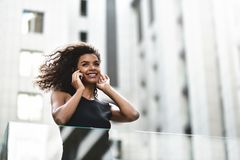 Den nätta affärskvinnan för det blandade loppet talar vid telefonen i stad arkivbild