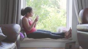 Den nätta afrikansk amerikankvinnan som sitter på fönsterfönsterbrädaklippet, spikar med spikar mappen Flickan som att bry sig om stock video