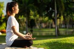 Den nätta asiatiska kvinnan som gör yoga, övar i parkera arkivfoton