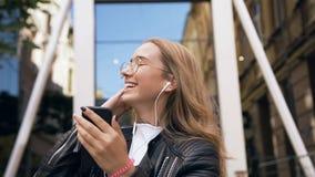 Den nätta attraktiva flickan i exponeringsglas använder lyssnande musik för apparat från appen av smartphonen i hörlurar, medan g lager videofilmer