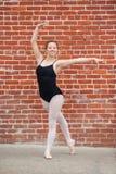 Den nätta balettflickan poserade framme av väggen för röd tegelsten Royaltyfri Foto