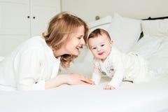 Den nätta barnmodern med henne behandla som ett barn i säng royaltyfri foto