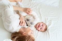 Den nätta barnmodern med henne behandla som ett barn i säng arkivbild
