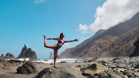 den nätta blonda flickan i svartöverkant kopplar av i yoga poserar lotusblomma på purpurfärgat mattt mot havvågor som kör på, vag stock video