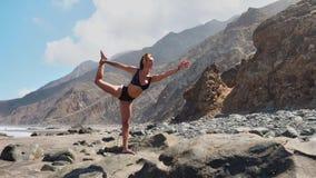 den nätta blonda flickan i svartöverkant kopplar av i yoga poserar lotusblomma på purpurfärgat mattt mot havvågor som kör på, vag lager videofilmer