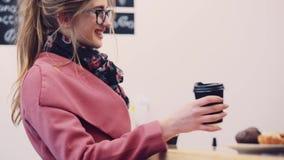 Den nätta blonda flickan med den tillfälliga frisyren och stilfulla exponeringsglas som står av cafeterian som väntar på hennes b stock video