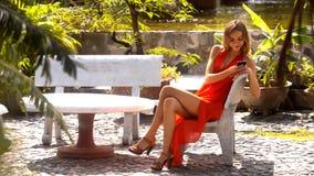 Den nätta blonda flickan surfar internet på telefonen parkerar in lager videofilmer