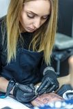 Den nätta blonda konstnären gör en tatuering med maximal koncentration arkivfoto