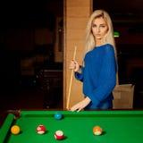 Den nätta blonda kvinnan med blåa ögon spelar billiard Arkivbild