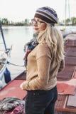 Den nätta blondinen i en tröja och ett tagande står på pir Royaltyfri Foto
