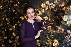 Den nätta brunetten i klänning står i studio med spisen arkivfoto