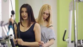Den nätta brunetten utbildar hennes händer under vägledning av lagledaren lager videofilmer