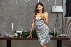 Den nätta brunettflickan i en glänsande grå aftonklänning som rymmer ett exponeringsglas av fruktsaft, står bredvid tabellen med  royaltyfri bild