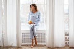 Den nätta brunettflickan i den ljusblå pajamaen sitter med ett exponeringsglas av ny fruktsaft i hennes hand på fönsterbrädan på  royaltyfri bild