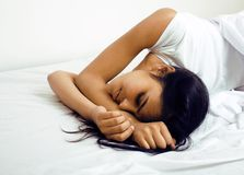 Den nätta brunettkvinnan i säng, välter sömn Arkivbilder
