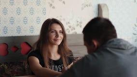 Den nätta brunettkvinnan lyssnar till hennes mansamtal Förälskade par har konversation, som de sitter i något trevligt ställe lager videofilmer