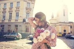 Den nätta brunettkvinnan med att fladdra hår i vind och solen blossar Royaltyfri Foto