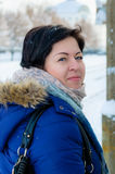 Den nätta brunettkvinnan med kort hår i vinterkläder på en gata i envänd ser Royaltyfri Fotografi