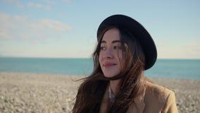 Den nätta brunettkvinnan står i solig strand i blåsväder, stående stock video