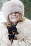 Den nätta damen kelar hennes lilla hund i vintertid Arkivbilder
