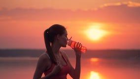 Den nätta damen med en hästsvans står nära en sjö och dricker sötvatten från en flaska lager videofilmer