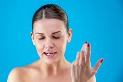 Den nätta europeiska unga ilskna brunhåriga kvinnan med sund ren hud, skrika som vinkar hennes armar, på en blått royaltyfria foton