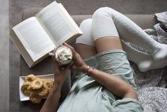 Den nätta flickaläseboken på soffan med varm choklad mjölkar hemma och kakor royaltyfria foton