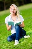 Den nätta flickaläseboken sitter på det gröna gräset arkivbild