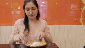 Den nätta flickan äter en pannkaka med glass i kafét, slut upp lager videofilmer