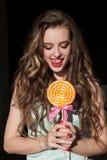 Den nätta flickan äter en stor söt klubba royaltyfria foton