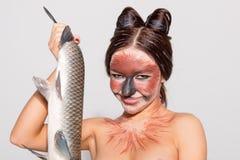 Den nätta flickan annonserar fisken arkivfoto