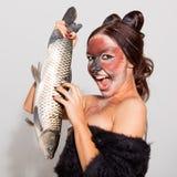 Den nätta flickan annonserar fisken arkivbild