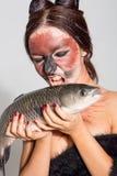Den nätta flickan annonserar fisken royaltyfri bild