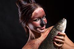 Den nätta flickan annonserar fisken arkivfoton