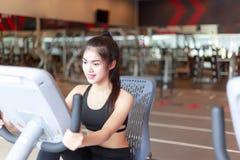 Den nätta flickan cyklar cykelmaskinen på sportidrottshallen charmin royaltyfri bild