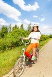 Den nätta flickan i cykelhjälm rider en cykel Royaltyfri Fotografi