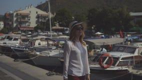 Den nätta flickan i hatt och solglasögon går på pir på bakgrunden av den härliga naturen arkivfilmer