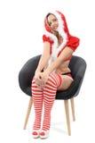 Den nätta flickan klädde som jultomten som sitter på fåtöljen royaltyfria foton