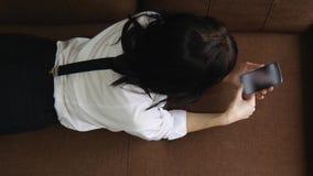 Den nätta flickan ligger på en soffa med mobiltelefonen som pratar sms som bläddrar internet lager videofilmer