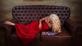 Den nätta flickan ligger på lädersoffan arkivfoto