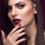 Den nätta flickan med den ovanliga frisyren, ljus makeup, röda kanter och manikyr planlägger Härlig le flicka Konst spikar Royaltyfri Fotografi