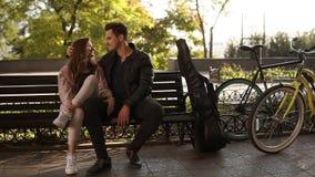 Den nätta flickan med långt brunt hår sitter med hennes stiliga brunettgrabb på parkerar bänken Stående av ett par som är förälsk lager videofilmer