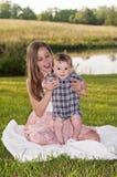 Den nätta flickan med långt sammanträde för blont hår på en filt med lyckligt behandla som ett barn pojken Royaltyfria Bilder