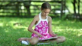 Den nätta flickan med minnestavladatoren sitter på gräset lager videofilmer