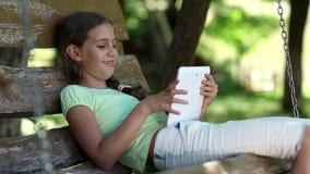 Den nätta flickan med minnestavladatoren sitter på gungabänken arkivfilmer